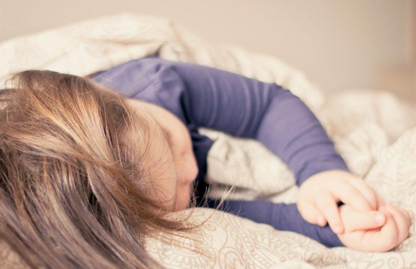 Kind beim Schlafen im Bett